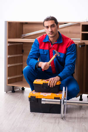 Young handsome male carpenter working indoors