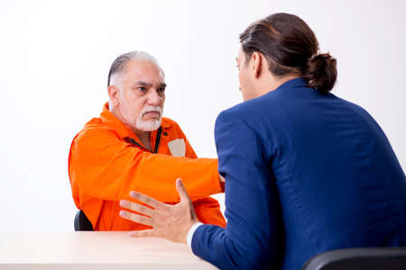 Old captive meeting with advocate in pre-trial detention Stock Photo