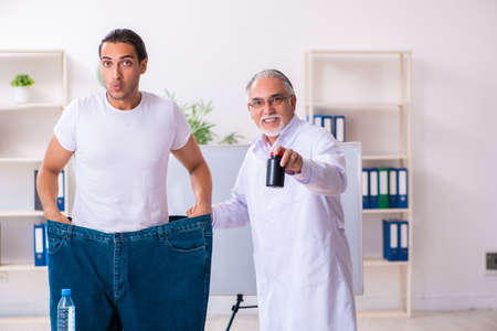 Doctor dietician and happy patient wearing large trousers