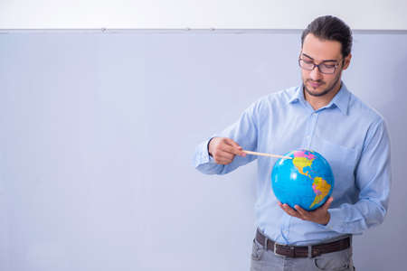 Young male geography teacher in front of whiteboard