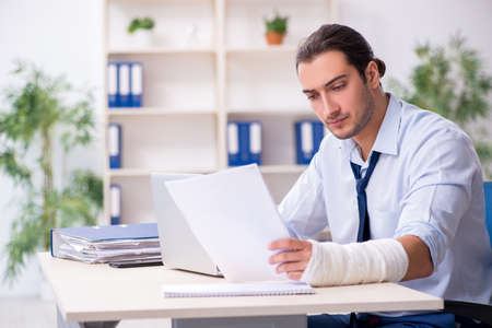 Injured male employee at workplace after accident Archivio Fotografico