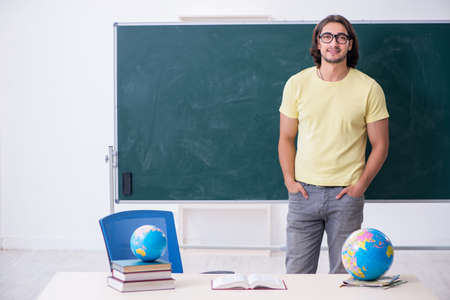 Young male geography teacher in front of blackboard