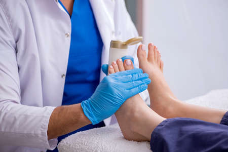 Podiatrist treating feet during the procedure