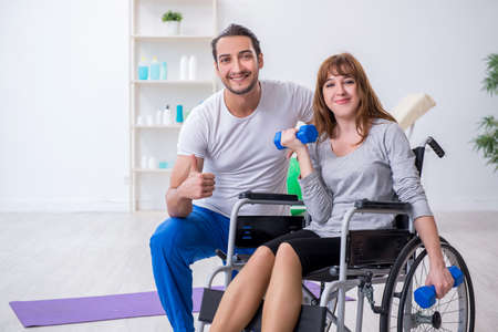 Woman in wheel-chair doing sport exercises with personal coach