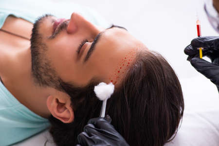 Young man visiting beautician in hair transplantation concept Фото со стока