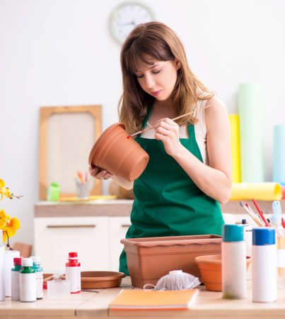 Young woman decorating pottery in workshop