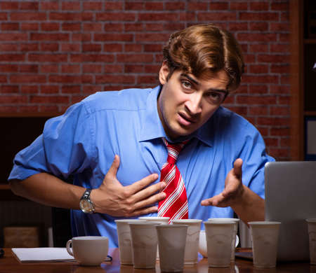 Young employee drinking coffee working at night shift