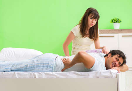 Woman doing massage to her husband in bedroom Banque d'images