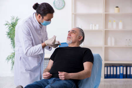 Old man visiting young doctor for plastic surgery Stok Fotoğraf