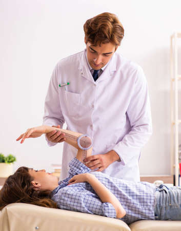 Male doctor checking joint flexibility with goniometer