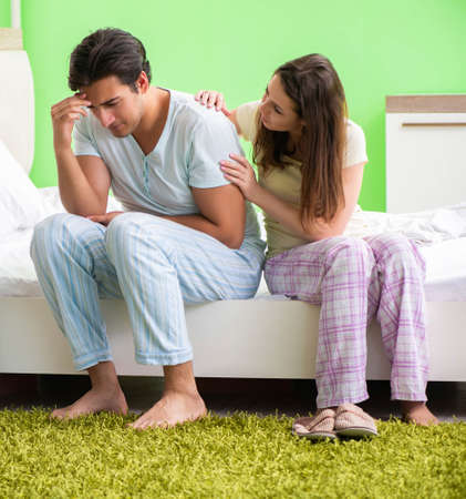 Young woman consoling disappointed impotent husband Imagens