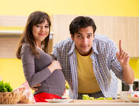 Man and pregnant woman preparing salad in kitchen