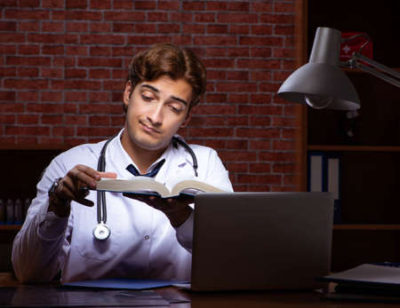 Young handsome doctor working night time at the hospital