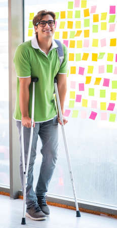 Young handsome student with crutches in conflicting priorities
