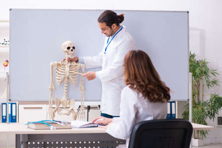 Young male teacher doctor, skeleton and female student in the cl Imagens