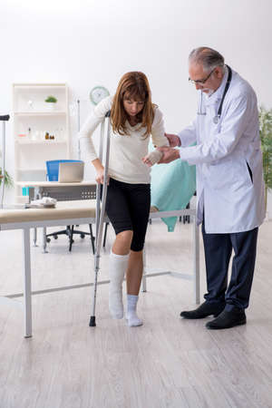 Young injured woman visiting experienced doctor traumatologist Banque d'images