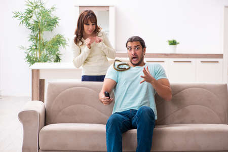 Young couple and snake in the flat Stock Photo
