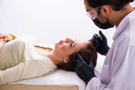 Young woman visiting beautician in hair transplantation concept