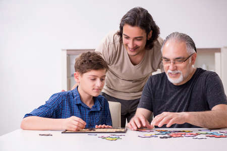 Three generations of family playing jigsaw puzzle game