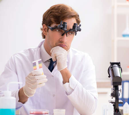The chemist in the lab checking with ph strips