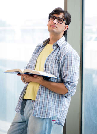Young handsome student standing at the window