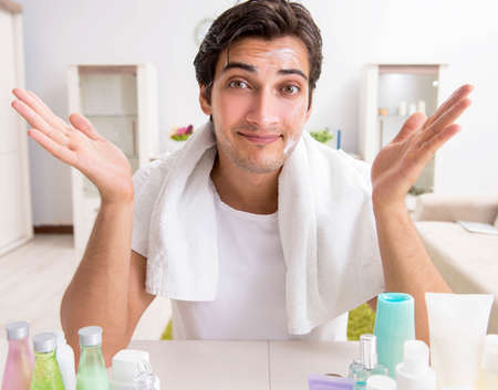 Young handsome man in the bathroom in hygiene concept Stock Photo