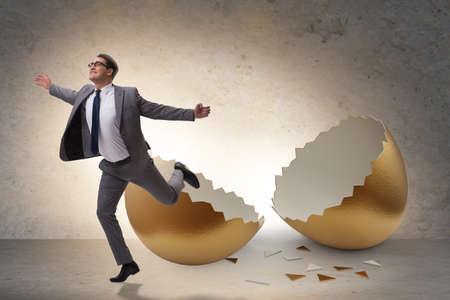 Businessman breaking out of golden egg