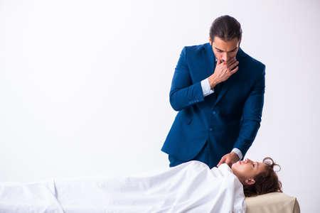 Police coroner examining dead body corpse in morgue Imagens