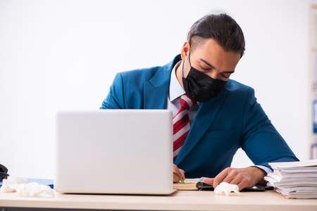 Sick male employee suffering at workplace from coronavirus Foto de archivo