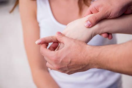 Injured woman visiting male doctor osteopath