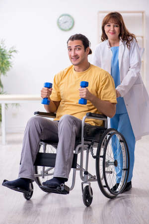 Young male patient in wheel-chair doing physical exercises