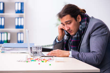 Young male employee suffering at workplace