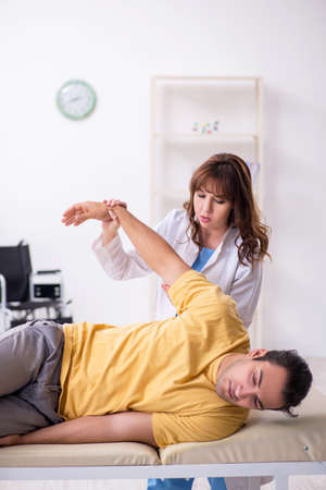 Injured man visiting young female doctor osteopath