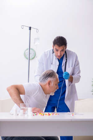 Young male doctor visiting old male patient at home