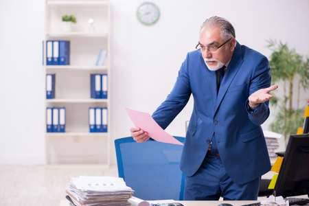 Old male employee and too much work in the office Фото со стока
