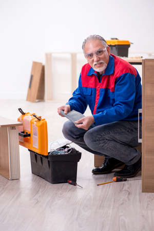 Old male carpenter working indoors