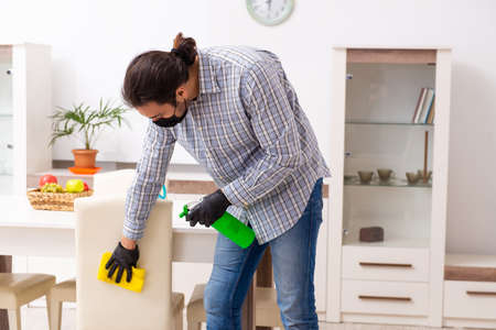 Young male contractor cleaning the house in coronavirus concept Фото со стока