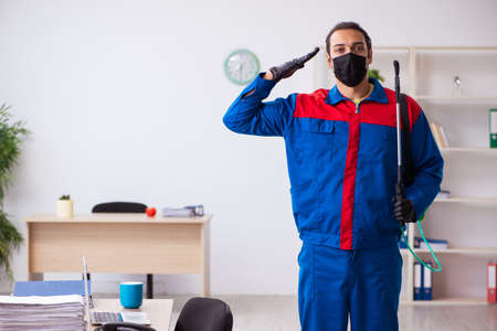 Young male contractor disinfecting office