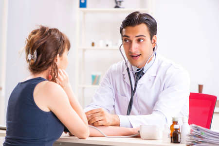 Young doctor checking womans blood pressure