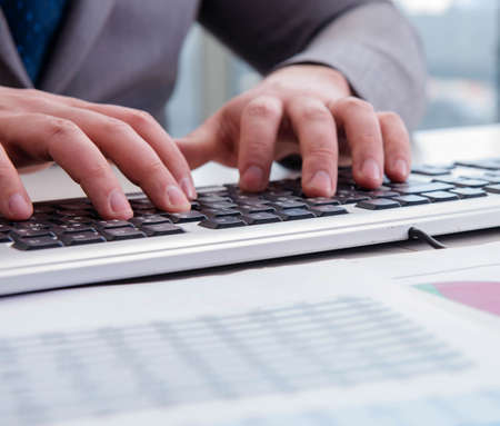 The finance professional working on keyboard with reports