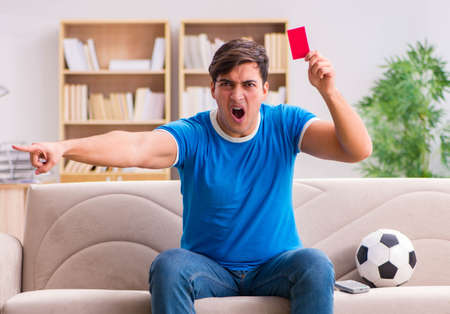 Man watching football at home sitting in couch