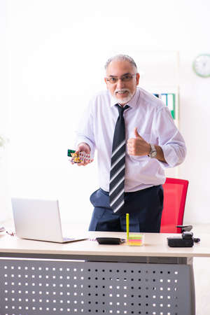 Old sick employee suffering at workplace