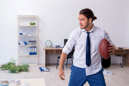 Young male employee throwing rugby ball in the office