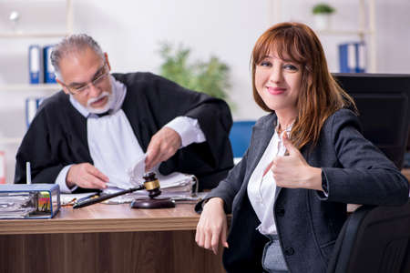 Old male judge and female client in the office