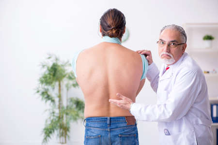 Young back injured man visiting experienced male doctor Zdjęcie Seryjne