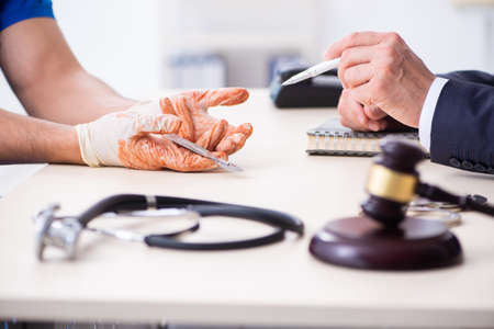 Male doctor in courthouse meeting with advocate
