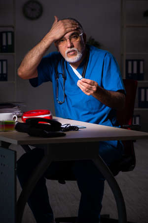 Aged male doctor in the hospital at night Stockfoto
