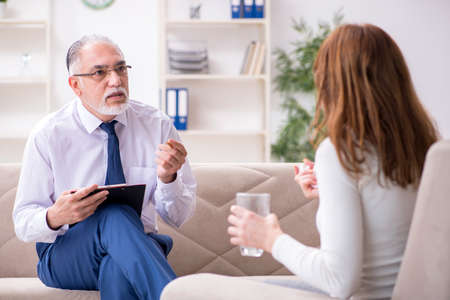 Young woman visiting old male doctor psychologist