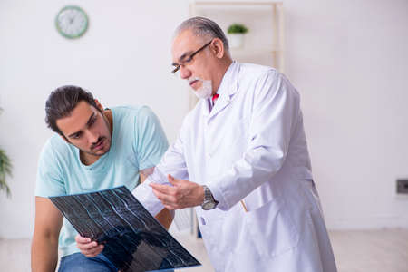 Young back injured man visiting experienced male doctor Stockfoto