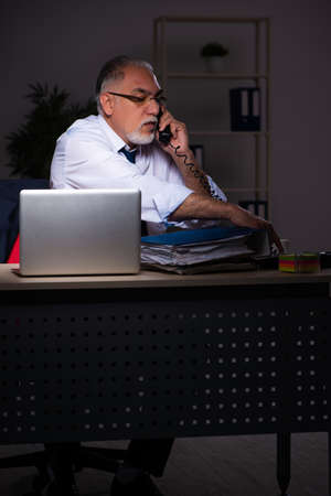 Old male employee working late at workplace